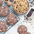 Chocolate cookies with walnuts and chocolate chips on table and cooling rack, top view, square - PhotoDune Item for Sale