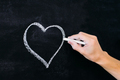 man's hand with white chalk drawing heart on blackboard as love symbol - PhotoDune Item for Sale
