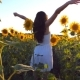 Young Girl Standing at the Field of Sunflowers and Raising Her Hands Up. Woman Enjoy By Landscape - VideoHive Item for Sale