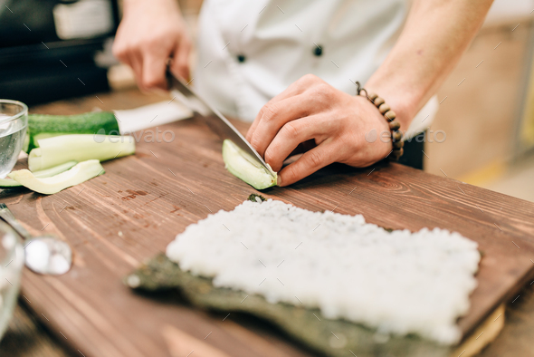 Male cook making sushi rolls on the kitchen - Stock Photo - Images