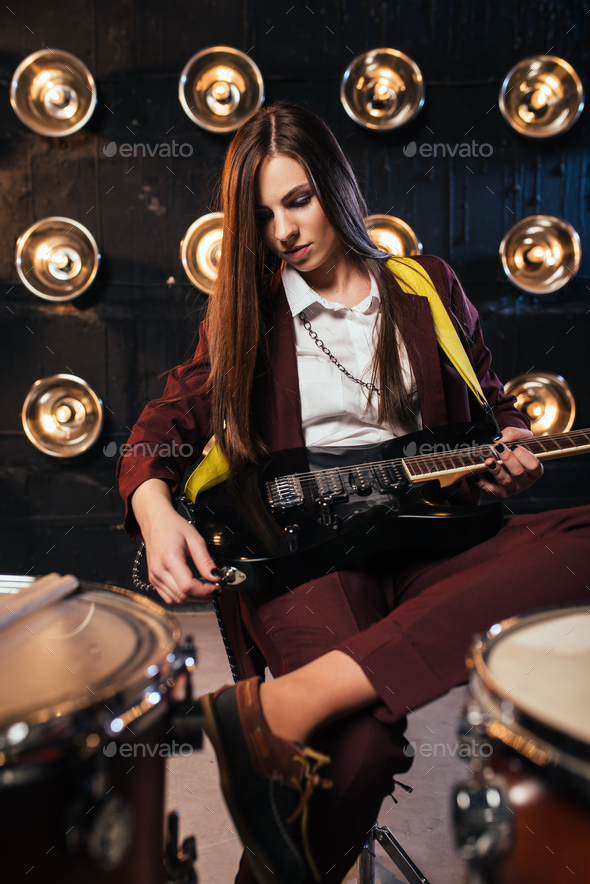 Female rock guitarist sitting behind the drum kit - Stock Photo - Images