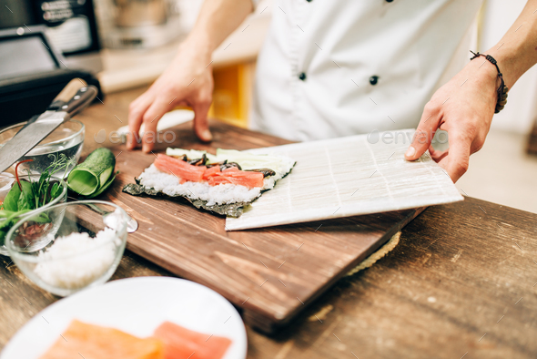 Male cook making sushi, asian kitchen - Stock Photo - Images