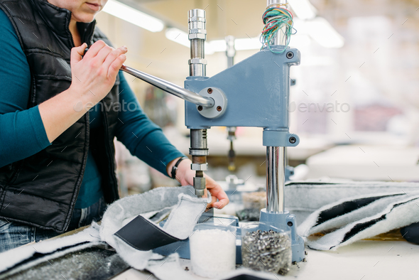 Female tailor works on riverting machine - Stock Photo - Images