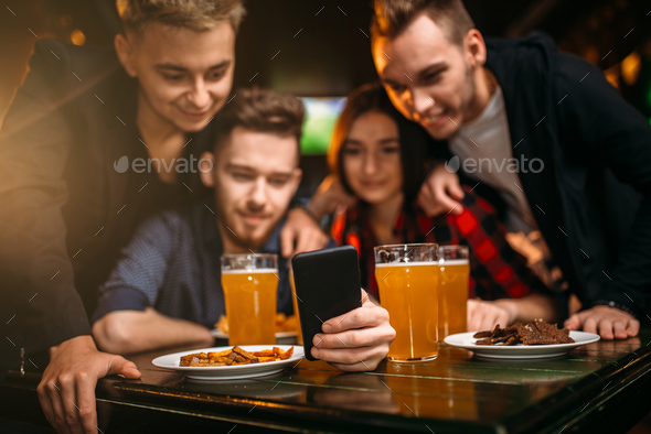 Fun company watches photo on phone in a sport bar - Stock Photo - Images