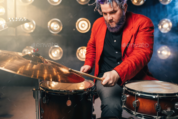 Bearded drummer in red suit, performing on stage - Stock Photo - Images