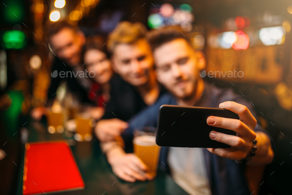 Happy football fans makes selfie at bar counter - Stock Photo - Images
