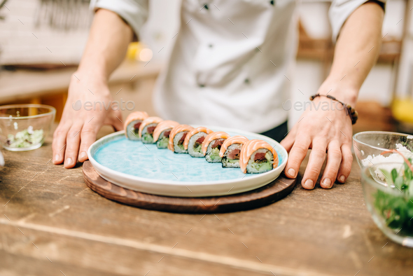 Man cooking sushi rolls, japanese kitchen - Stock Photo - Images