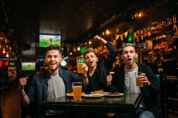 Men at the table with beer, crisps and crackers - Stock Photo - Images