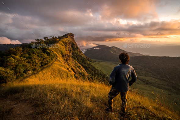 Young traveler looking at beautiful sunrise over the mountain - Stock Photo - Images