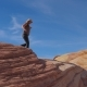 Tourist Woman Hiking Down the Crest Hill with Colorful Red Rocks - VideoHive Item for Sale