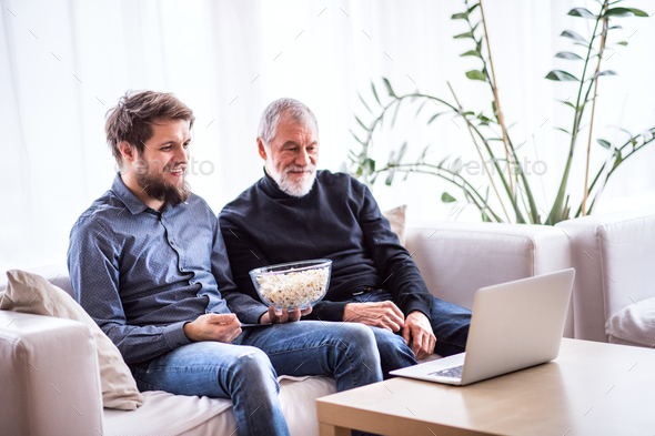 Hipster son and his senior father with laptop at home. - Stock Photo - Images