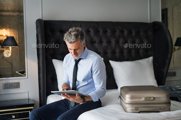 Mature businessman with tablet in a hotel room. - Stock Photo - Images