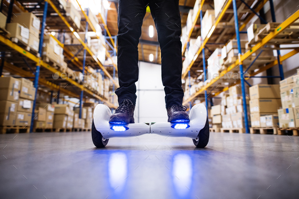 Male warehouse worker on hoverboard. - Stock Photo - Images
