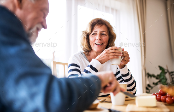 Senior couple eating breakfast at home. - Stock Photo - Images