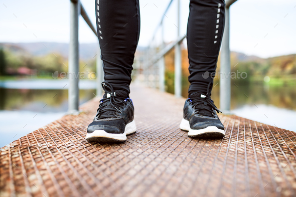 Legs of young runner standing on a pier. - Stock Photo - Images