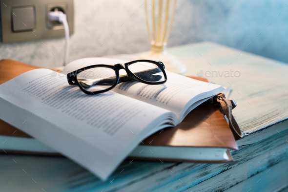 A lamp and a book on a bedside table in a hotel room. - Stock Photo - Images