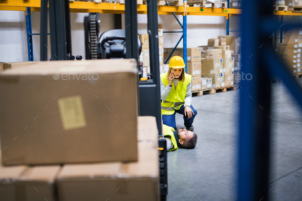 Warehouse workers after an accident in a warehouse. - Stock Photo - Images