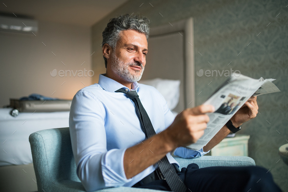 Mature businessman reading newspapers in a hotel room. - Stock Photo - Images