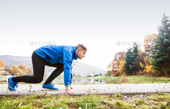 Runner at the lake on asphalt path in steady position. - Stock Photo - Images
