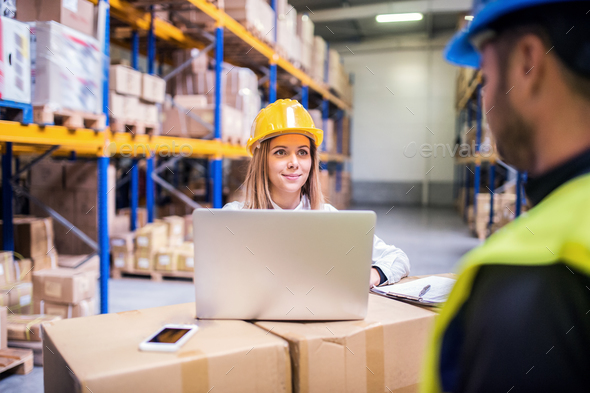 Young warehouse workers with laptop working together. - Stock Photo - Images