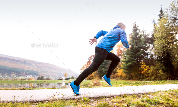 Athlete at the lake running against colorful autumn nature. - Stock Photo - Images