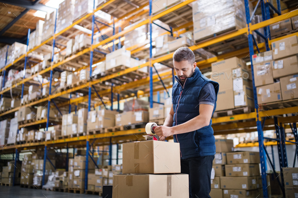 Male warehouse worker sealing cardboard boxes. - Stock Photo - Images