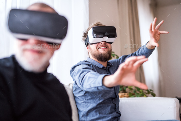 Hipster son and his senior father with VR goggles at home. - Stock Photo - Images