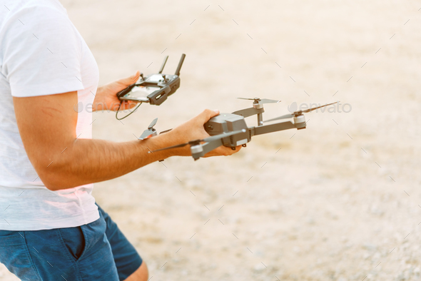 Young man holding drone before flight at nature - Stock Photo - Images