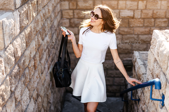 Young beautiful woman against a stone wall - Stock Photo - Images