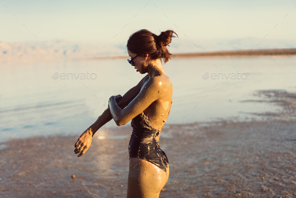 A young woman enjoying the natural mineral mud - Stock Photo - Images