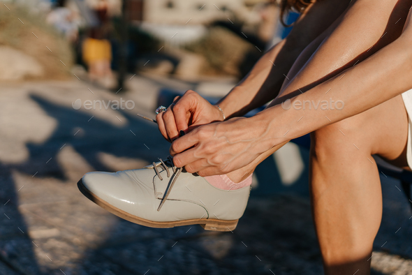 Young woman tying her shoes in the park - Stock Photo - Images