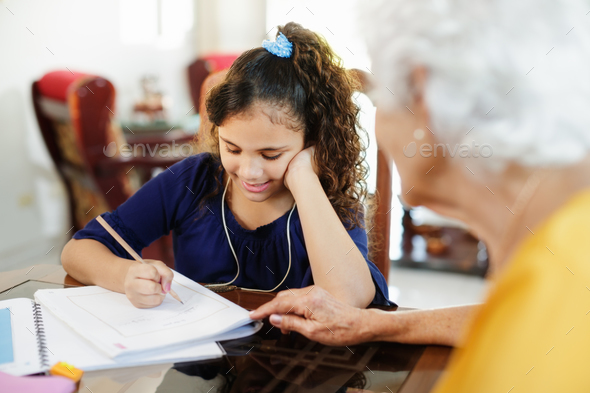 Elderly Woman Helping Little Girl Doing School Homework - Stock Photo - Images