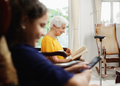 Granddaughter Using Mobile Phone And Grandma Reading Book - PhotoDune Item for Sale