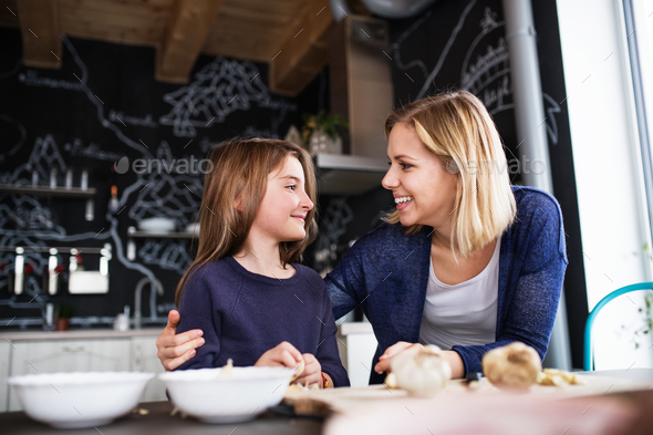 A small girl with her mother cooking at home. - Stock Photo - Images
