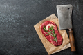 Raw rib eye steak and butcher knife on blackboard - PhotoDune Item for Sale