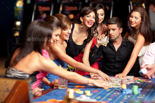 happy caucasian friends playing roulette in casino - Stock Photo - Images