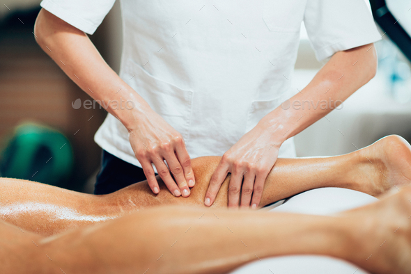 Sports massage. Physical therapyst massaging leg of young male a - Stock Photo - Images