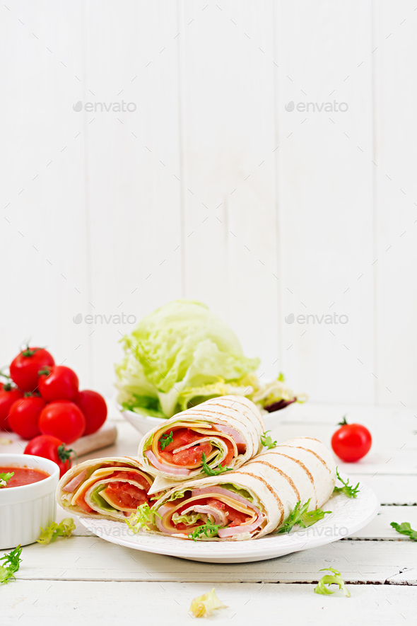 Tortilla wrap with ham, cheese and tomatoes on a white wooden background - Stock Photo - Images