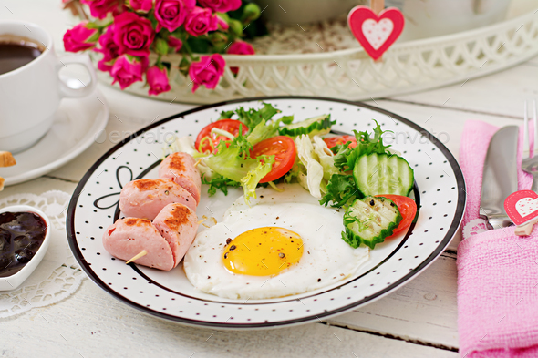 Breakfast on Valentine's Day - fried egg in the shape of a heart, toasts, sausage - Stock Photo - Images
