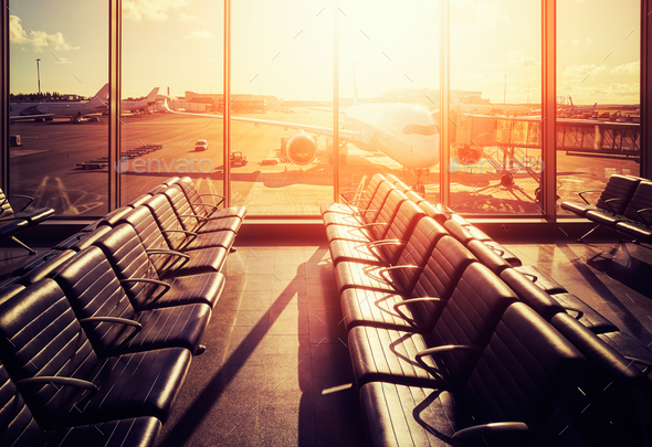 Empty seats in an airport departure hall at sunset. - Stock Photo - Images