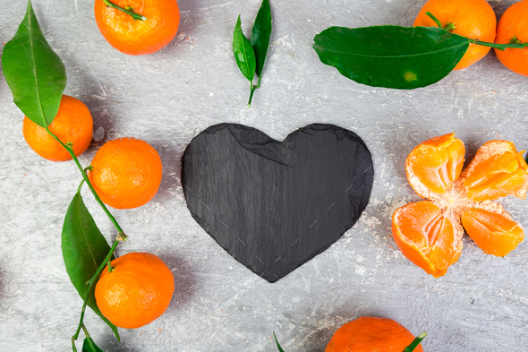 Tangerine around with black slate heart shaped. - Stock Photo - Images