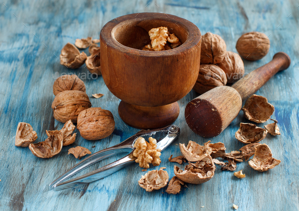 Fresh walnuts and mortar on a blue wooden table - Stock Photo - Images