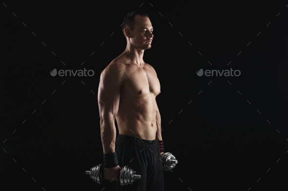 Strong athletic man with dumbbell showes naked muscular body - Stock Photo - Images