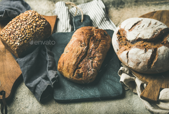 Various bread loaves on grey concrete background - Stock Photo - Images