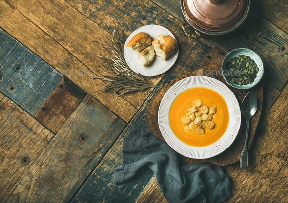 Warming pumpkin cream soup with croutons and seeds, copy space - Stock Photo - Images