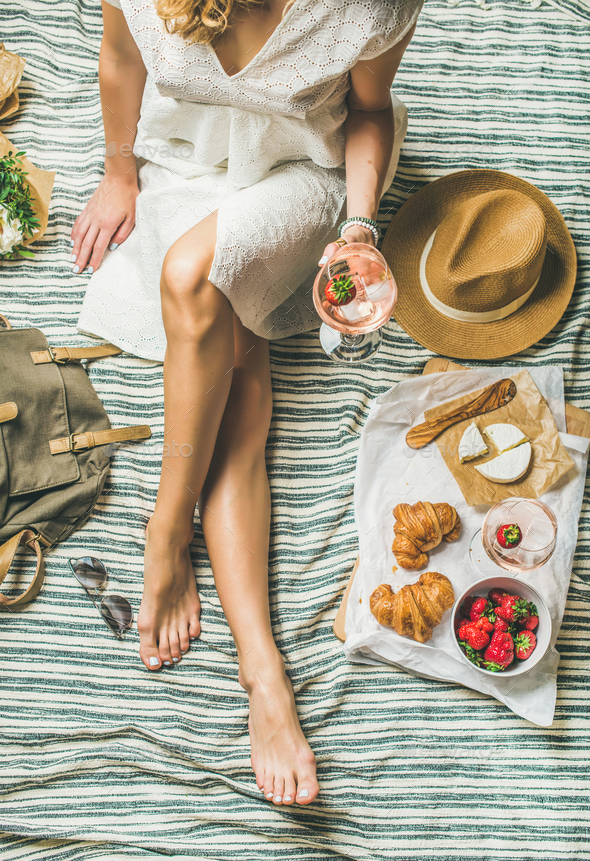 Woman in dress sitting on blanket with wine and snacks - Stock Photo - Images
