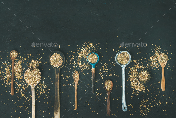 Various kitchen spoons full of green buckwheat grains, copy space - Stock Photo - Images