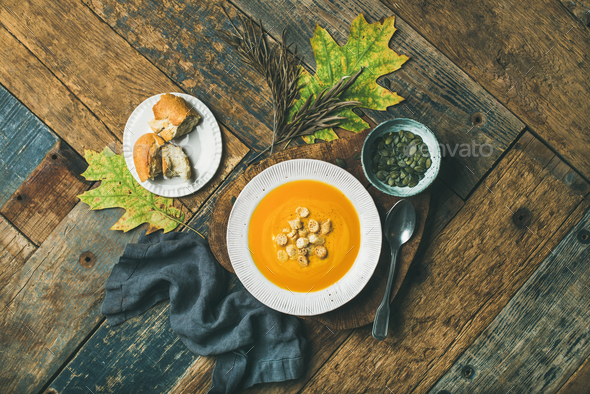 Warming pumpkin cream soup with croutons and seeds, top view - Stock Photo - Images