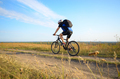 Male cyclist with backpack driving by rural dirt road outdoors - PhotoDune Item for Sale