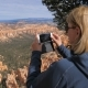 Woman Tourist Standing On Lookout Point In Bryce Canyon And Photos To Smartphone - VideoHive Item for Sale